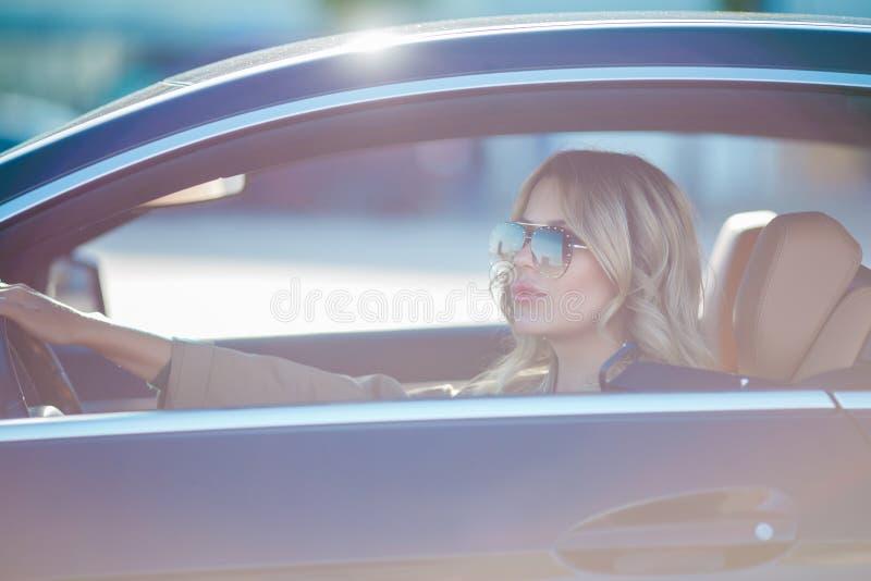Bild av den härliga blondinen i solglasögon som sitter i svart bil royaltyfria bilder