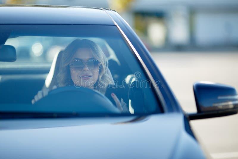 Bild av den härliga blondinen i solglasögon som sitter i svart bil under dag royaltyfri bild