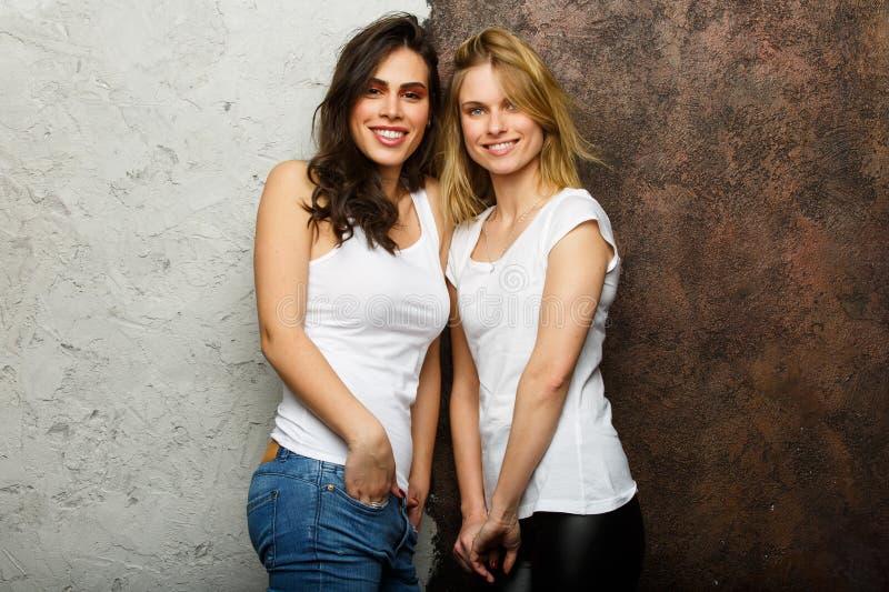 Bild av den härliga brunetten och blondinen i vita T-tröja arkivfoto