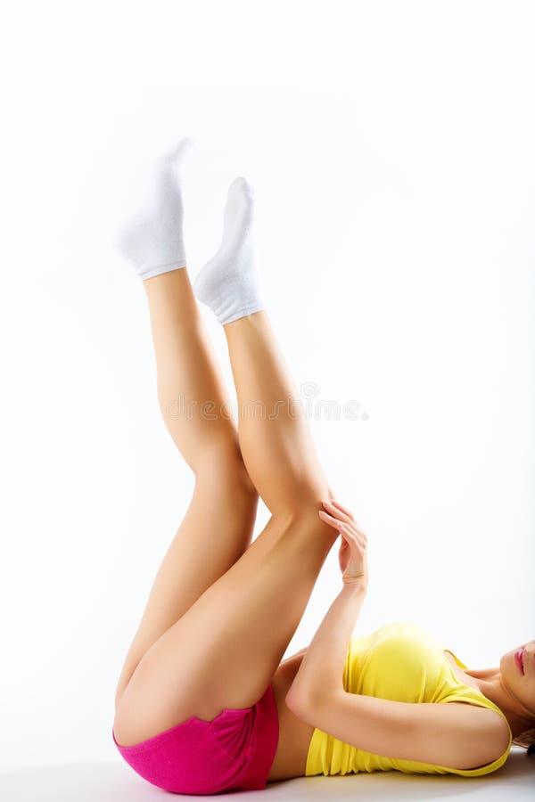 Bild av den härliga kvinnan i bomullsundrewearen som trycker på henne ben royaltyfri fotografi