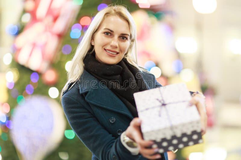 Bild av den härliga kvinnan i lag med gåvaasken på bakgrund av julgranen fotografering för bildbyråer