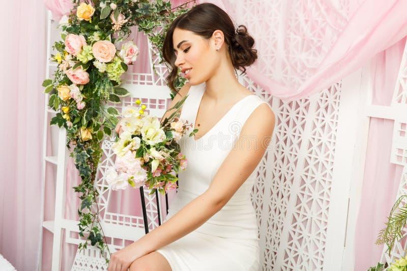 Bild av den härliga kvinnan i den vita klänningen på bakgrund av blommor royaltyfri fotografi