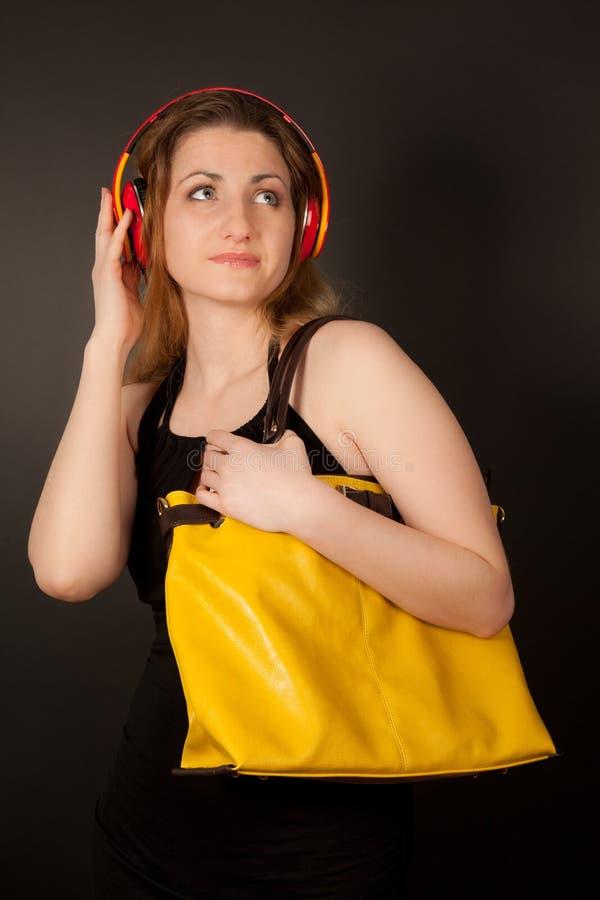 Bild av den härliga kvinnan med hörlurar som ser upp arkivbilder