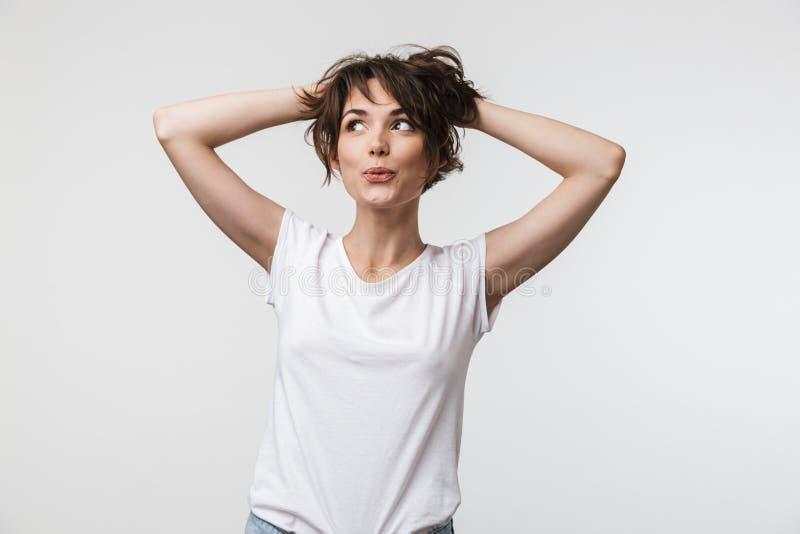 Bild av den härliga kvinnan med kort hår i grundläggande t-skjorta som ler och griper hennes huvud fotografering för bildbyråer