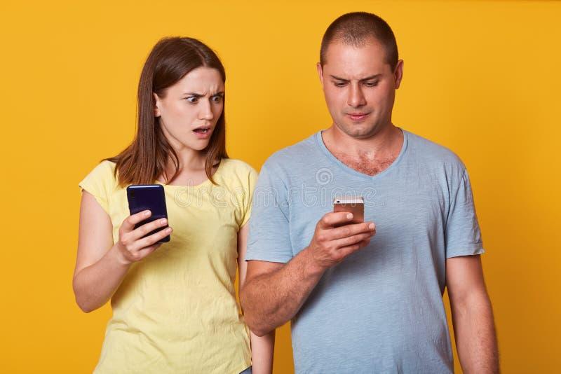 Bild av den karismatiska gulliga modellen som imponeras av hennes pojkvänmeddelanden som brett ser skärmen av hans telefon, öppna royaltyfri foto