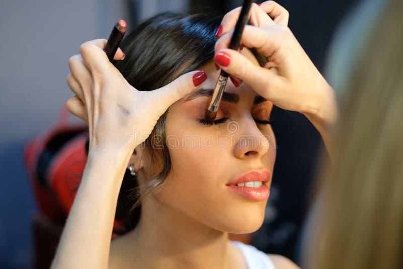 Bild av den kvinnliga modellen och stylisten med borsten arkivfoton