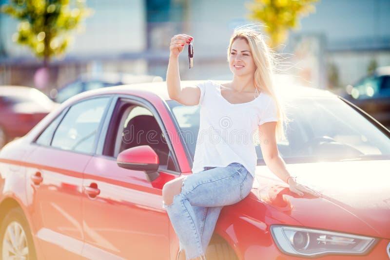 Bild av den lyckliga blonda flickan med tangenter som står nära den röda bilen på sommardag arkivbilder