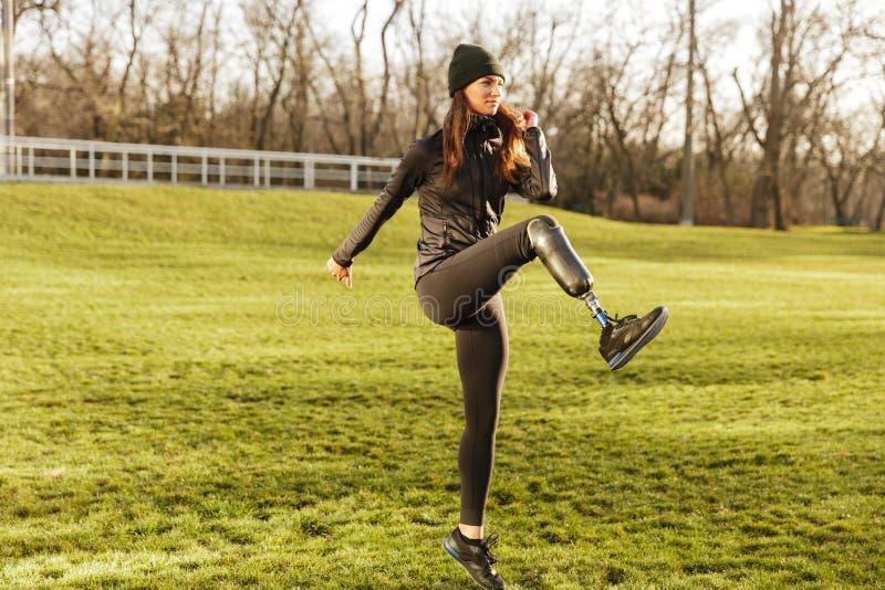 Bild av den lyckliga handikappade kvinna20-tal i träningsoverall som gör sportar arkivfoton