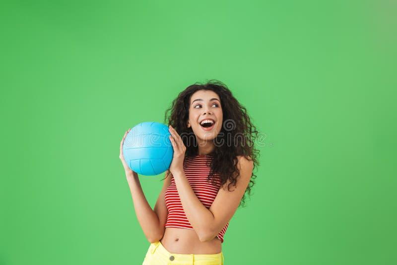Bild av den lyckliga kvinna20-tal som ler och rymmer salvabollen, medan stå mot grön bakgrund royaltyfri bild