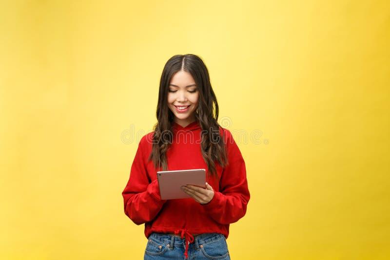 Bild av den lyckliga tonårs- flickan med isolaten för minnestavlaPCdator på gul bakgrund arkivfoto