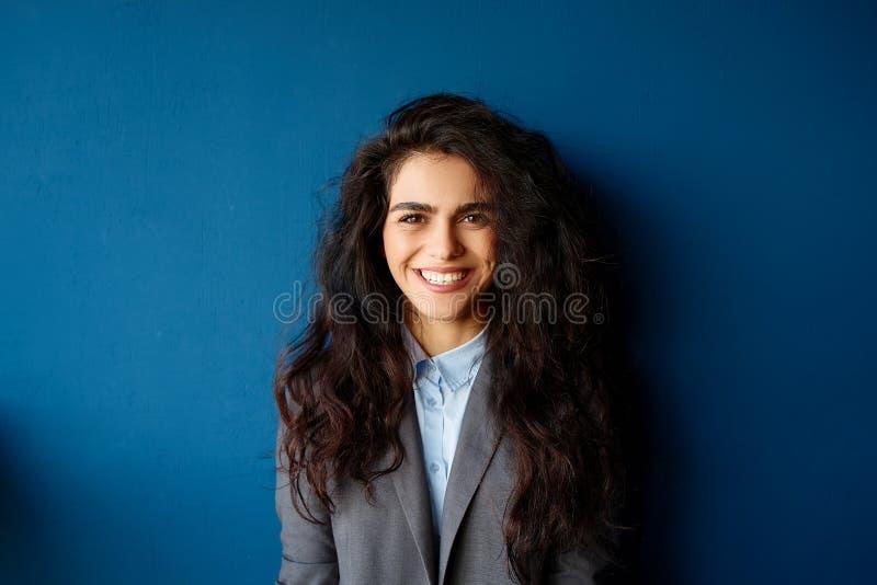 Bild av den lyckliga unga affärskvinnan i regeringsställning som åt sidan ser royaltyfri bild