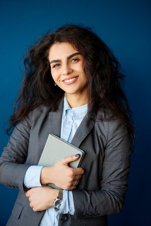 Bild av den lyckliga unga affärskvinnan i regeringsställning som åt sidan ser royaltyfri fotografi