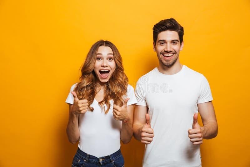 Bild av den lyckliga den ungdomarmannen och kvinnan i grundläggande klädlaug royaltyfri fotografi