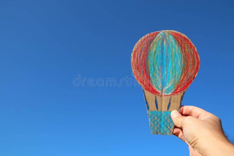 Bild av den manliga handen som rymmer ballongen för varm luft mot himlen fantasi och framgångbegrepp royaltyfria foton