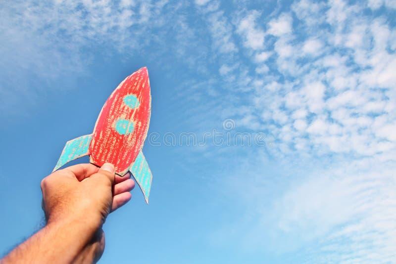 Bild av den manliga handen som rymmer en raket mot himlen fantasi och framgångbegrepp royaltyfria bilder
