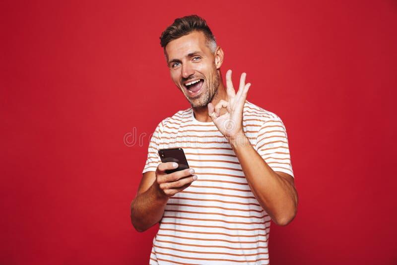 Bild av den orakade mannen i randig t-skjorta som ler och rymmer sma arkivfoto