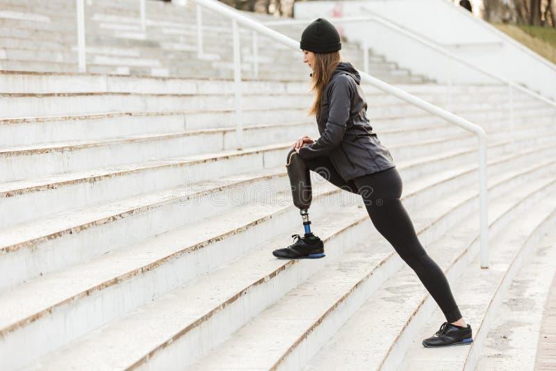 Bild av den rörelsehindrade rinnande flickan med det prosthetic benet i sportswear royaltyfri bild