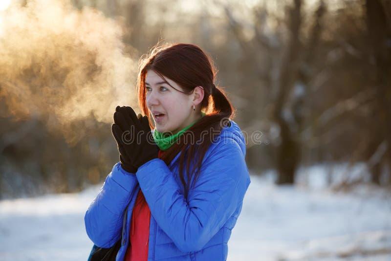 Bild av den sportiga kvinnan som värme hennes händer i vinterskog arkivfoton