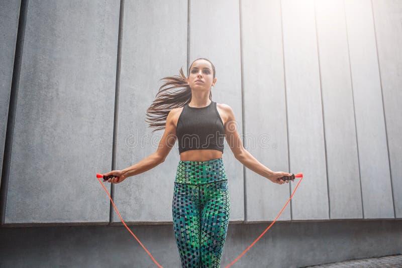 Bild av den starka och kraftiga unga kvinnan som hoppar med repet Hon ser rättfram Modellen bär sportkläder royaltyfria bilder
