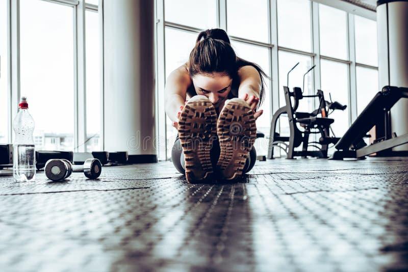 Bild av den starka sportkvinnan att göra sporten som sträcker övningar i idrottshall arkivbild