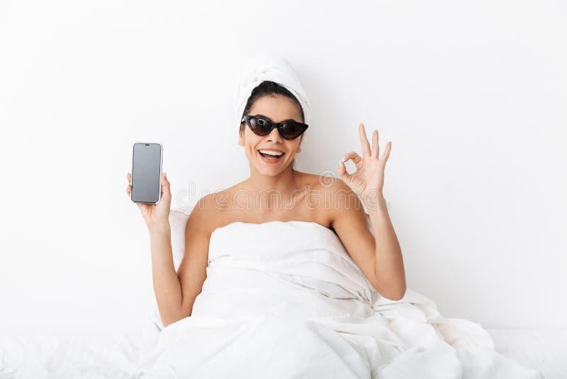 Bild av den stilfulla kvinna30-tal som bär solglasögon som slås in i filten som ligger i säng och rymmer mobiltelefonen royaltyfri fotografi