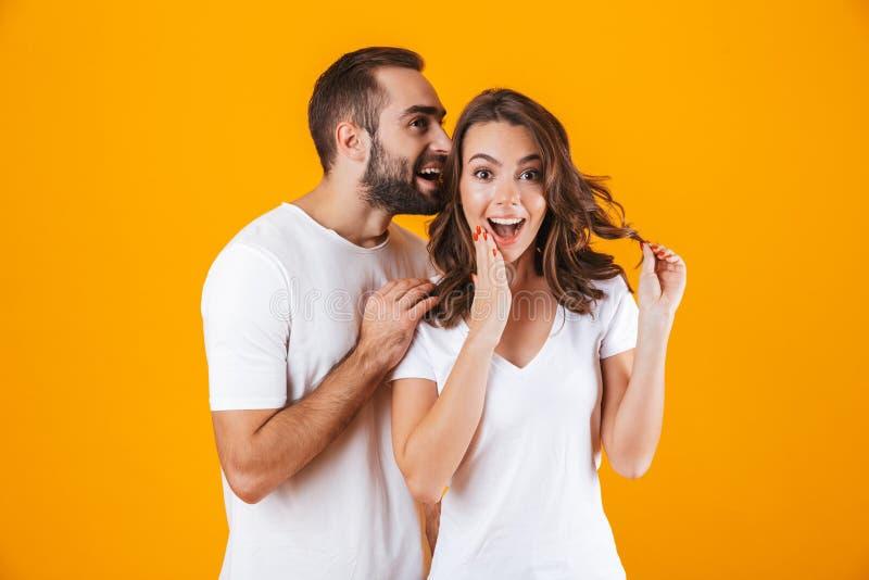 Bild av den stiliga mannen som viskar hemligt eller intressant skvaller till kvinnan i hennes öra som isoleras över gul bakgrund royaltyfri foto