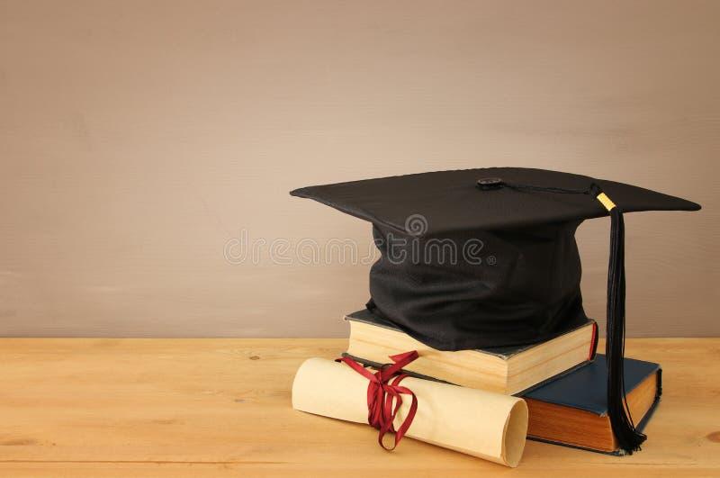Bild av den svarta hatten för avläggande av examen över gamla böcker bredvid avläggande av examen på träskrivbordet tillbaka begr arkivfoto