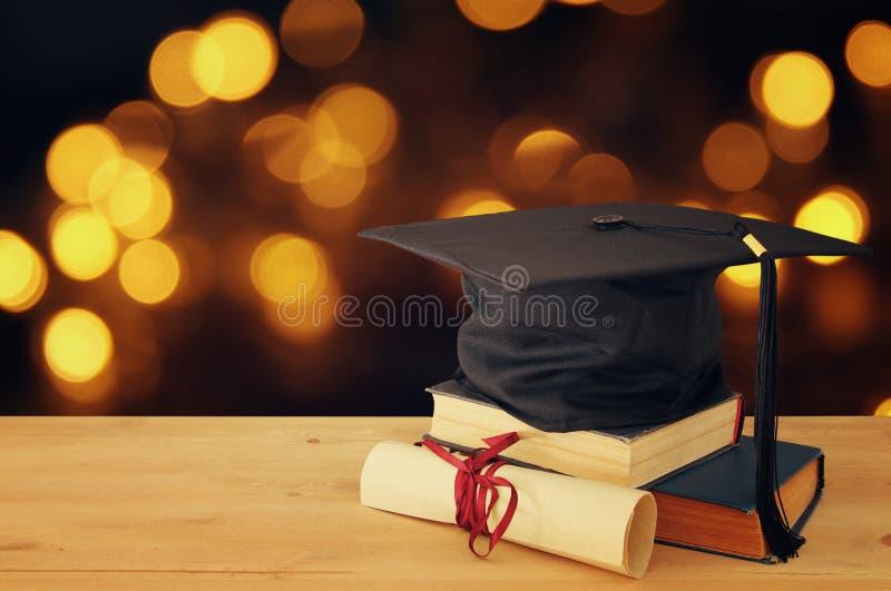 Bild av den svarta hatten för avläggande av examen över gamla böcker bredvid avläggande av examen på träskrivbordet tillbaka begr arkivbild