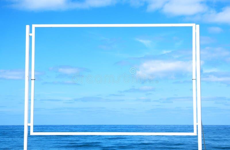 Bild av den tomma vita affischtavlan på stranden i framdel av det blåa havet och himlen För modell och annonsering arkivbilder