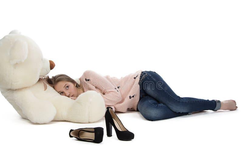 Bild av den tonårs- flickan som ligger med nallebjörnen arkivbild