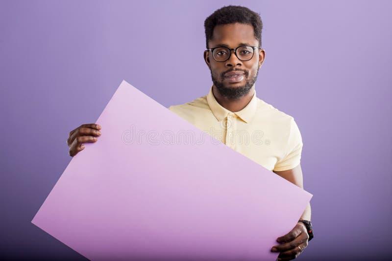 Bild av den unga afrikansk amerikanmannen som rymmer det tomma br?det p? violett bakgrund fotografering för bildbyråer
