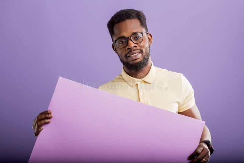 Bild av den unga afrikansk amerikanmannen som rymmer det tomma br?det p? violett bakgrund royaltyfria bilder