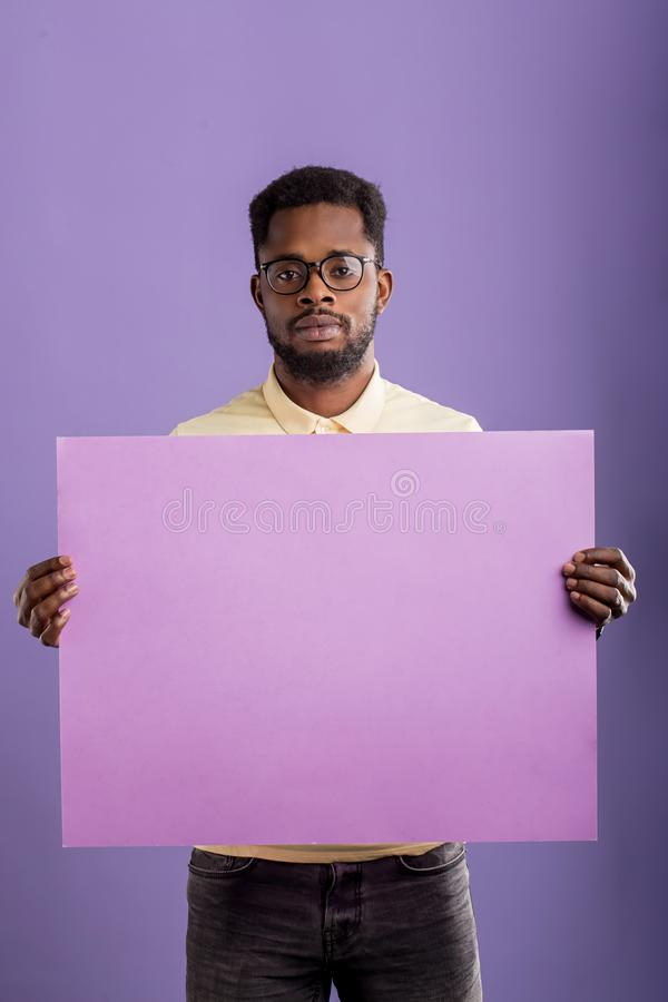 Bild av den unga afrikansk amerikanmannen som rymmer det tomma br?det p? violett bakgrund arkivfoto