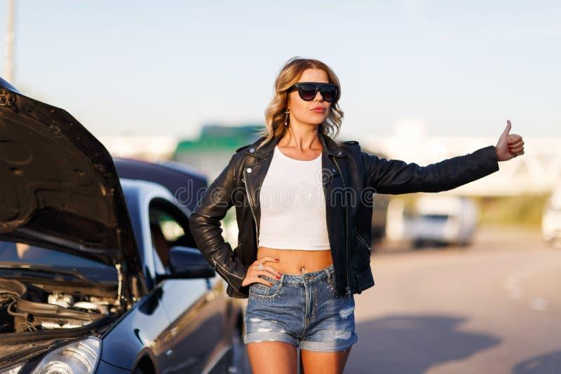 Bild av den unga blonda flickan som stoppar bilen på gatan arkivfoton