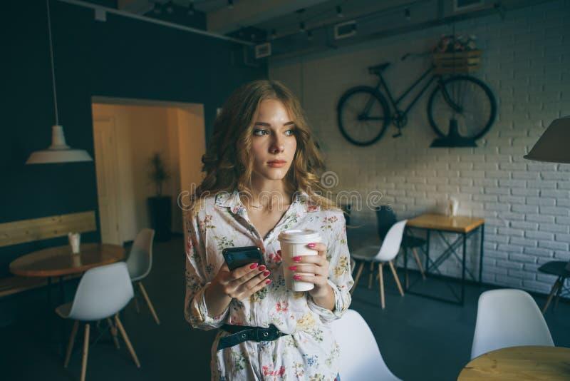 Bild av den unga gulliga blonda flickan med en kopp kaffeinnehavtelefon och en skrivatext, härlig yong kvinna med ljust arkivfoton
