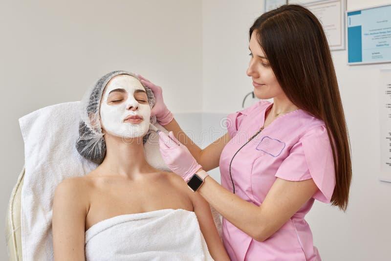 Bild av den unga kvinnlign med framsidan som skalar maskeringen, brunnsortskönhetbehandling Kvinna som får ansikts- omsorg av kos arkivfoto