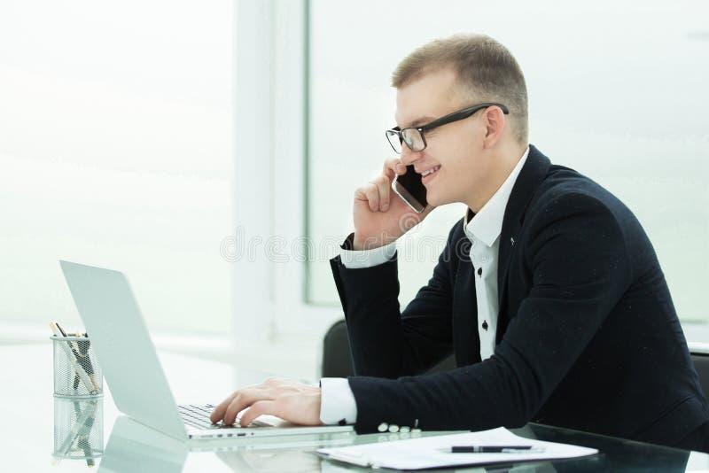 Bild av den unga mannen som använder en smartphone och le Se smartphonen arkivfoton