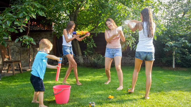 Bild av den unga modern f?r lycklig gladlynt barnwuth som spelar med vattenvapen och tr?dg?rdhuset Familj som spelar och har royaltyfri fotografi