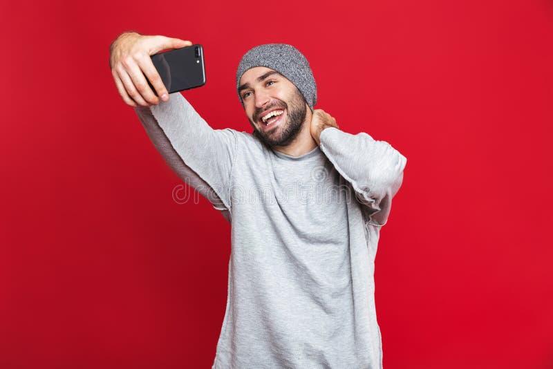 Bild av den upphetsade mannen som skrattar, medan ta selfiefotoet på mobiltelefonen som isoleras över röd bakgrund arkivbilder
