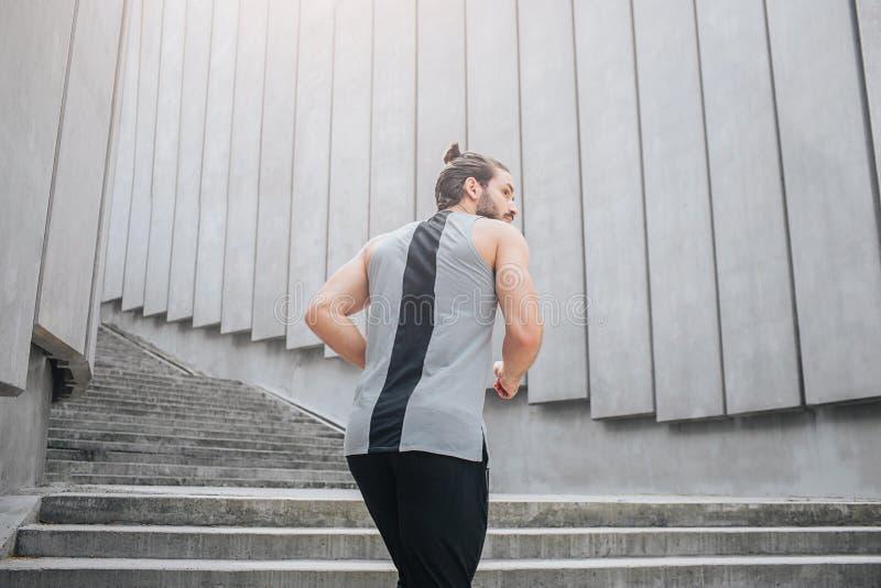 Bild av denhaired unga mannen som joggar upp på trappa Han ser till rätten Grabben bär sportlikformign Han är stark och arkivfoton