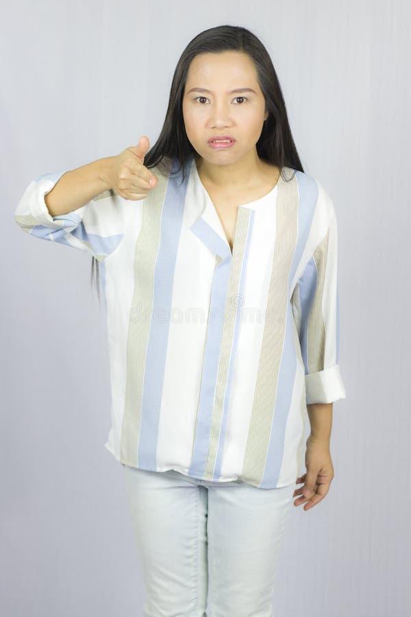 Bild av det ilskna anseendet f?r ung kvinna som isoleras ?ver gr? bakgrund se kameran royaltyfri foto