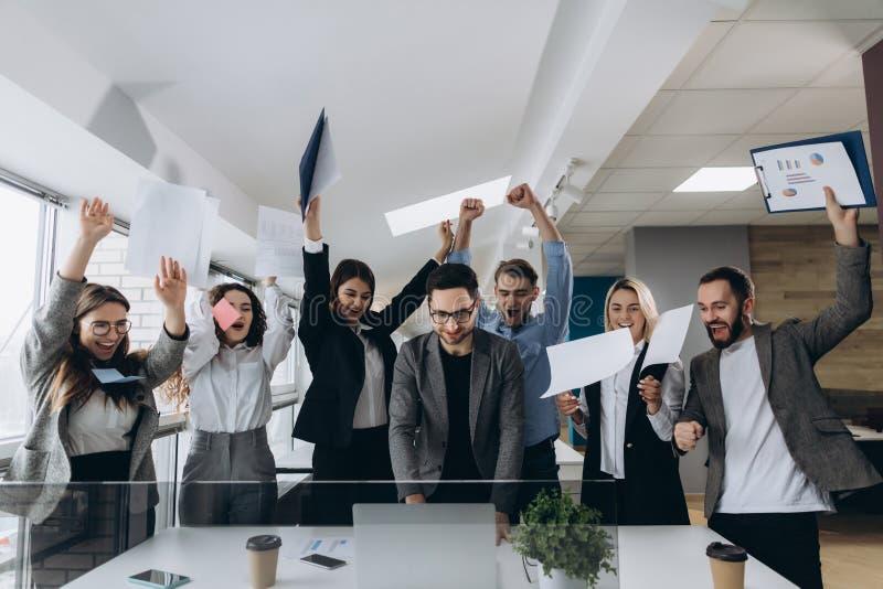Bild av det lyckliga affärslaget som i regeringsställning firar seger Det lyckade affärslaget kastar stycken av papper i modernt  arkivfoto