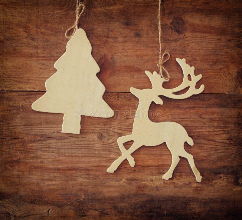 Bild av det trädekorativa den julträdet och renen som hänger på ett rep över träbakgrund arkivfoto