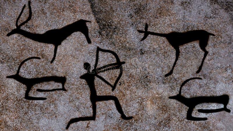 Bild av en forntida man Vagga målningar i grottan som göras ockran arkivfoto