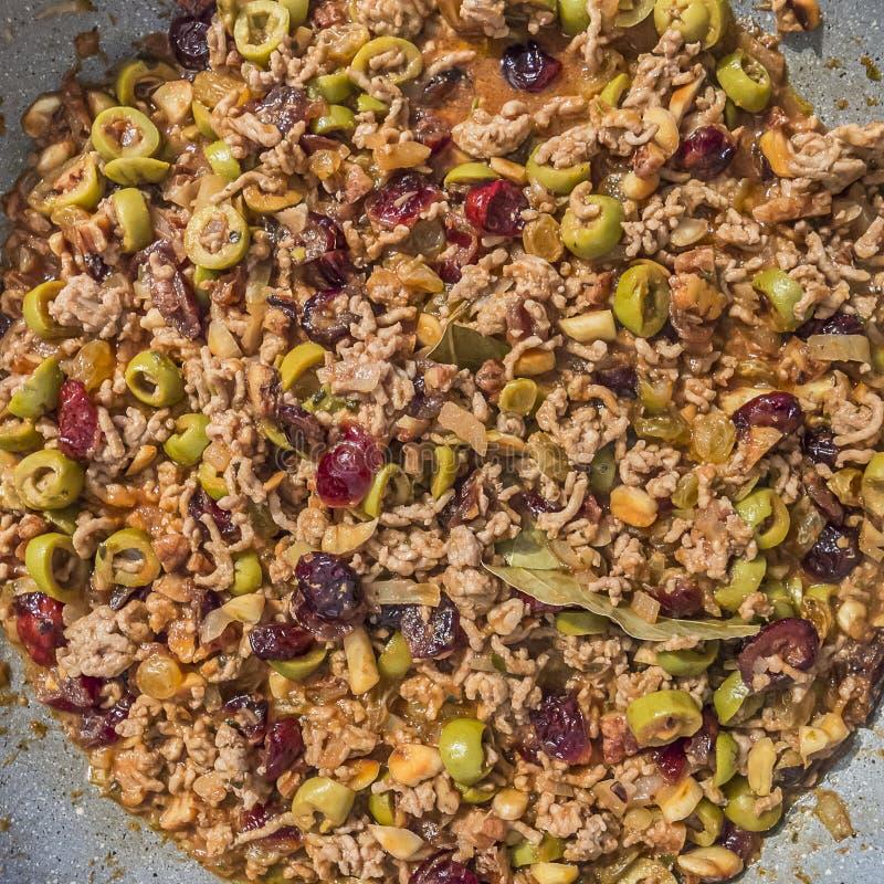 Bild av en fyllning med jordkött, oliv, russin, tranbär, valnötter, mandlar, lagerbladen och kryddor royaltyfri fotografi