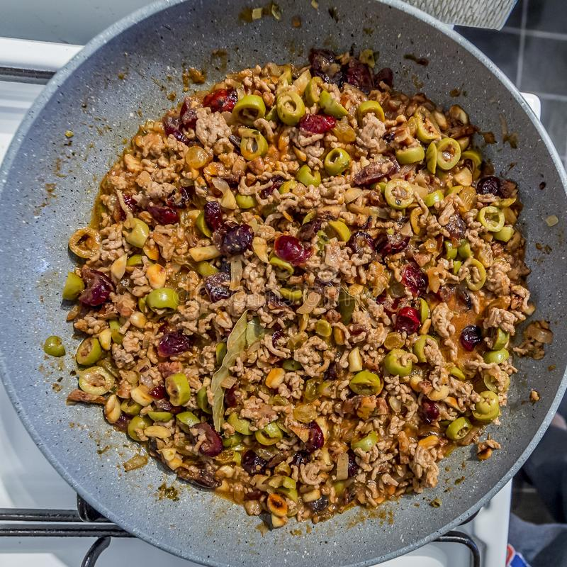 Bild av en fyllning med jordkött, oliv, russin, tranbär, valnötter, mandlar, lagerbladen och kryddor som är i en panna fotografering för bildbyråer