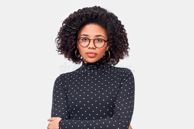 Bild av en ganska afrikansk ung kvinna, som bär tillfälliga kläder och ögonkläder Afro Hona i svart, lång skjorta som ställer arkivfoto