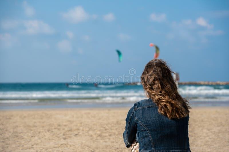 Bild av en kvinna på stranden som ser två kitesurfers i havet arkivfoton