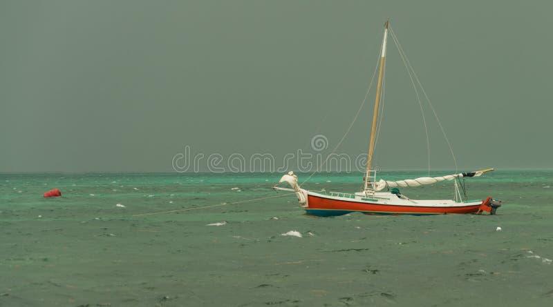 Bild av en liten segelbåt på stormiga hav royaltyfri fotografi
