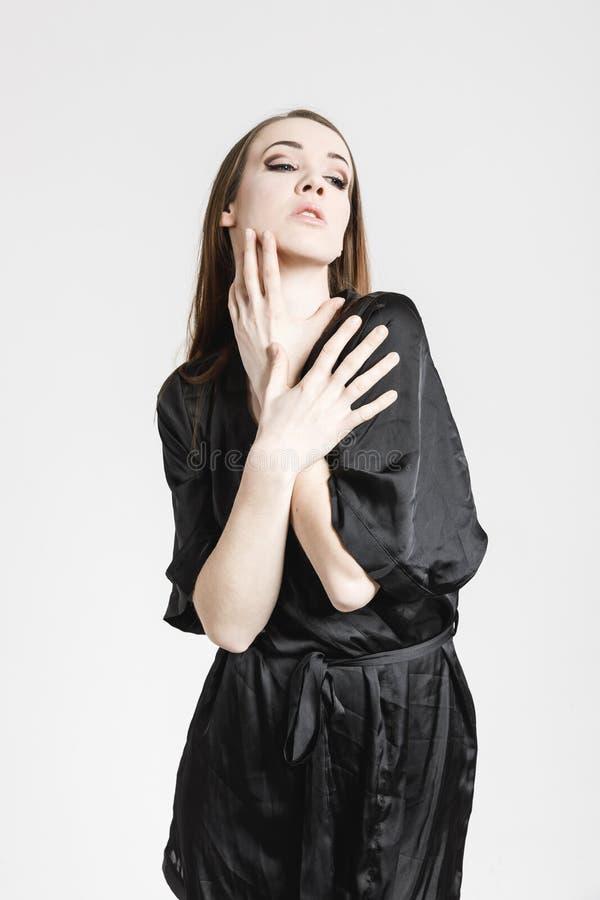 Bild av en ?lskv?rd ung kvinna i svart kl?nning royaltyfri foto